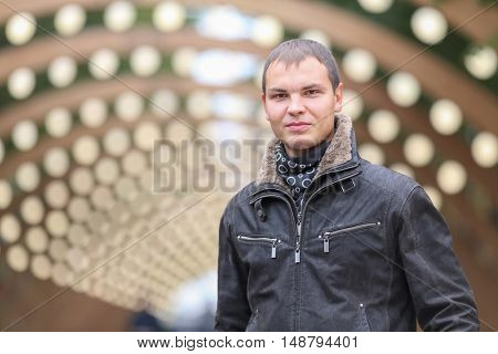 half length portrait of young man in black jacket on background of lights installation main park alley