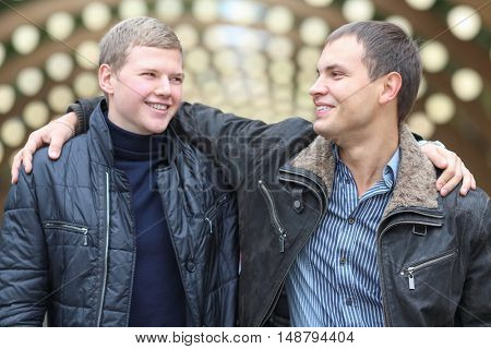portrait of two smiling friends on background of lights installation main park alley, close-up, focus on right man