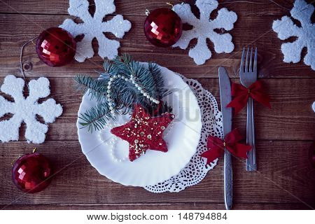 on a wooden table is a plate lay beside a fork and knife decorated with Christmas toys