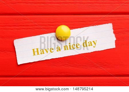 Sheet of paper on red wooden background, have a nice day