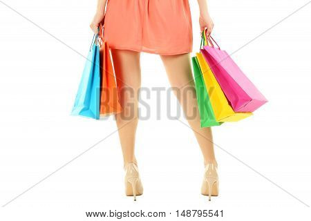 Female Legs With Beige High Heels And Shopping Bags On A White Background