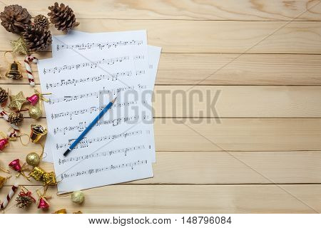 Create music sheet note paper by myself.Top view pencil music sheet note paper and Christmas decoration on wood background.