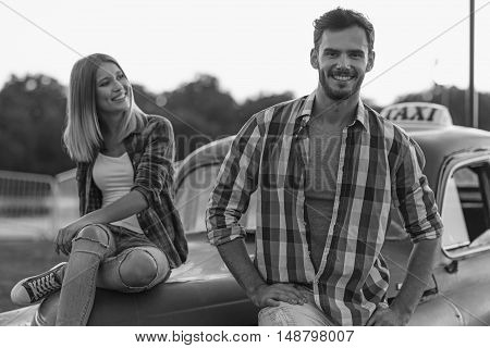 black and white, woman looking at her boyfriend while he looking into camera