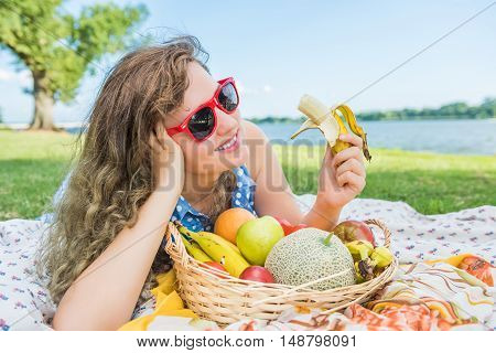 Young woman in red sunglasses lying down and smiling eating banana and fruit during picnic near Potomac River in Washington, DC