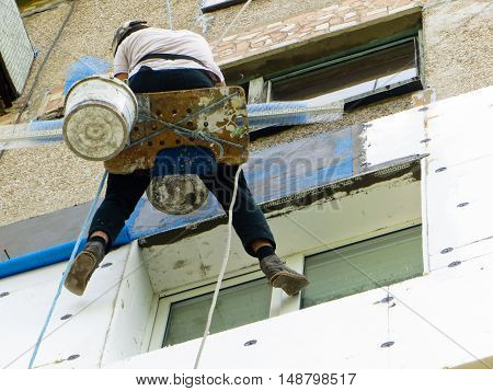 rope access worker spreading mortar over styrofoam insulation