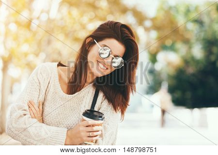 Young woman wearing woolen sweater walking in the autumn city street and drinking take away coffee in paper cup. Breakfast on the go.