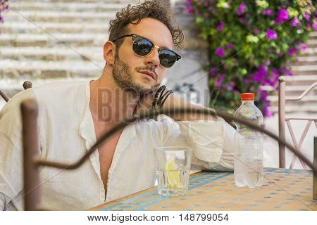 Portrait of stylish good-looking man in sunglasses holding bottle of water at table in cafe