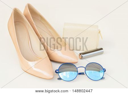 Nude colored high heels still life with wallet, blue sun glasses and lipstick