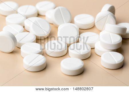 Heap of round white pills on beige background