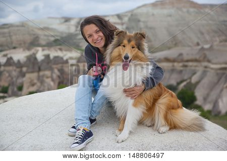 Young happy girl sitting with collie dog in Cappadocia valley