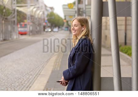 Smiling Young Woman Waiting For Her Bus