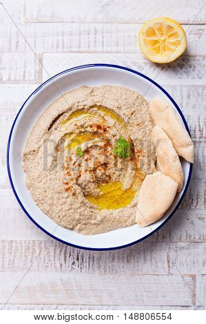 Homemade hummus with lemon oil and spices on a bowl on a wooden background top view