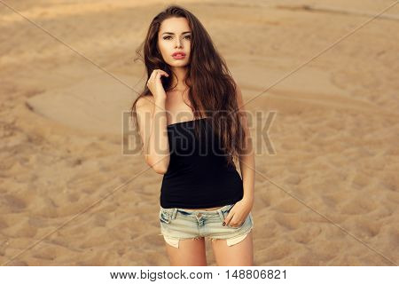 Outdoor portrait of young stylish woman wearing black t-shirt or top and blue jeans shorts standing on the beach. Pretty sexy hipster girl