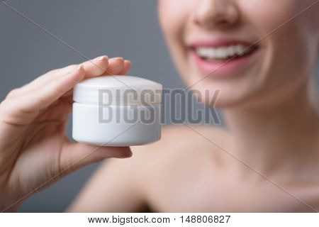 cream mockup, close up of a cosmetic jar in woman hands