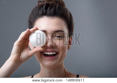 skin care concept, close up of a young happy girl holding cosmetic jar