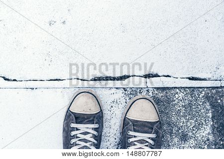 Pair of worn sneakers on concrete floor painted in white as copy space