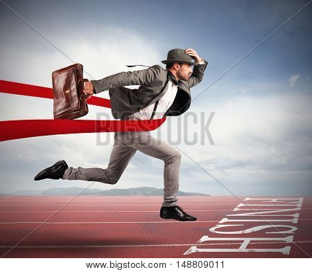 Businessman with bag goes beyond the red ribbon at the arrival of a race