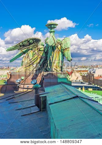 The bronze sculpture of angels holding the torch on the rooftop of the St Isaac's Cathedral with the city's skyline on the background St Petersburg Russia.