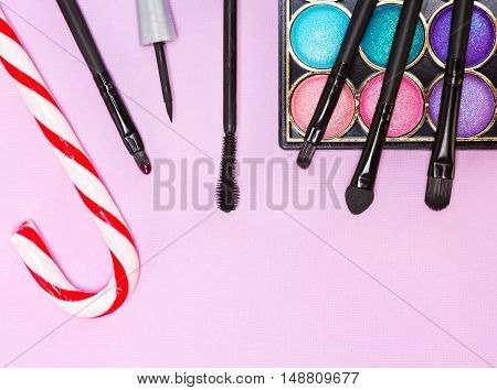 Christmas makeup cosmetics. Bright color glitter eyeshadow, black eyeliner, mascara, red lip gloss, make up brushes and applicator with candy cane on pink textured background
