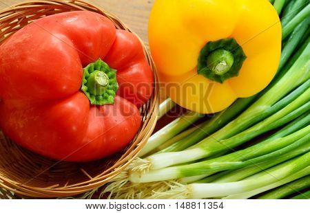 red and yellow paprika in basket with spring onions