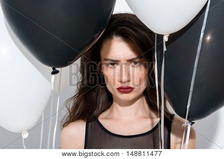 beautiful and upset brunette standing on white background