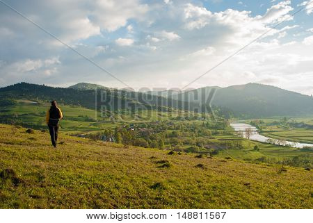 A man inspects the village in the valley. Mountain valley. Mountain farmland. Mountain peaks. Agricultural grounds. Bridge over river. Carpathians, Ukraine