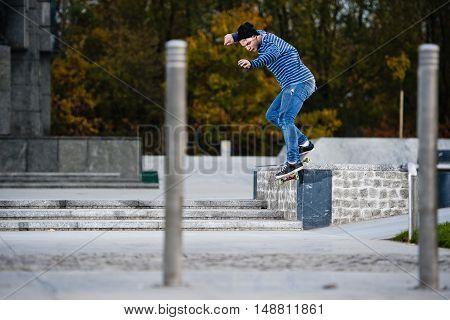 Boy doing skateboard trick smithgrind on ledge