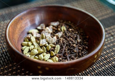 Cardamon, cloves and areca nuts in wooden bowl