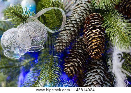 Christmas decorations on artificial Christmas tree. Transparent glass Christmas balls.