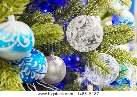 Christmas decorations on artificial Christmas tree. Blue Christmas toy balls with patterns.