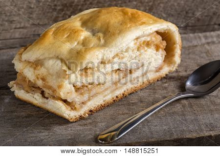 Apple strudel on rustic wooden background with spoon