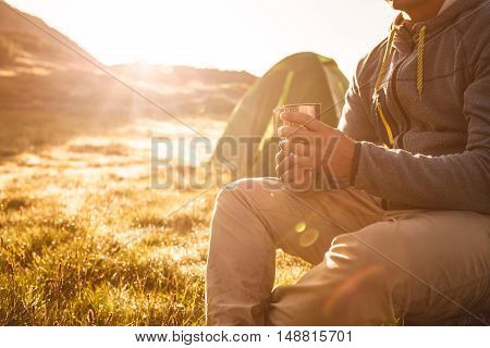 Young man drinking tea at sunrise in mountains. Mountain camping concept.