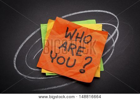 Who are you question - handwriting on a sticky note against black paper