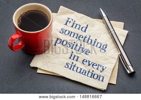 Find something positive in every situation - handwriting on a napkin with a cup of espresso coffee