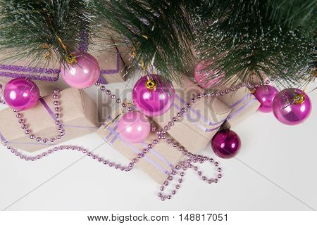 Pink balls on the green branches of a Christmas tree