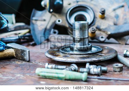 Old, oiled wheel hub lies on a wooden table. car repair in the field and at home.