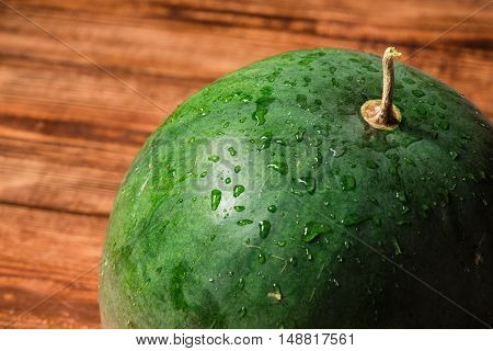 Green small watermelon with sprays on surface