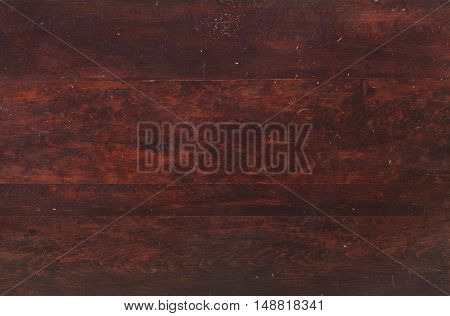 Reddish wood of an old tabletop viewed from above