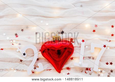 Christmas and New Year 2017 background. Red heart light bulbs and confetti on white fabric.