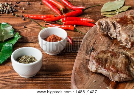 Two cooked steak with different condiment and metal knife on wooden table.