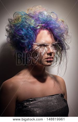 Beautiful girl with creative make up very long false eyelashes and professional hair colouring on dark background