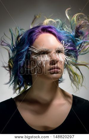 Portrait of a beautiful girl with professional hair colouring creative make up and very long false eyelashes