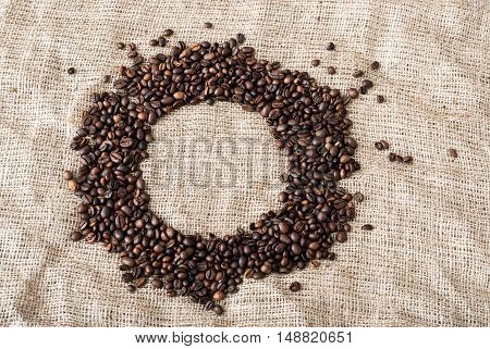 the coffee grains scattered on a table near a cup with coffee