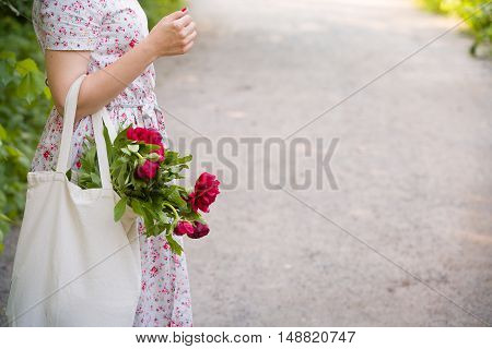 Woman holding beautiful red peonies. Girl with bouquet of flowers in her hands. Closeup of hands holding bunch of peonies.