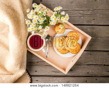Cozy breakfast in spring or early autumn tea, freshly baked scones and bouquet of field's daisy and fascinating book. In wooden tray, top view, Copy space