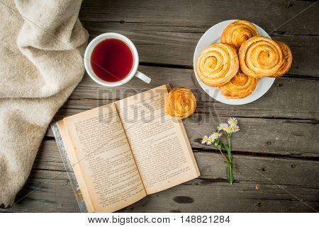Cozy breakfast in spring or early autumn tea, freshly baked scones and bouquet of field's daisy and fascinating book. Copy space, top view