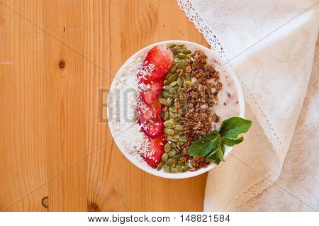Breakfast berry smoothie bowl topped with strawberry pumpkin seeds coconut muesli and fresh mint. Strawberry banana smoothie bowl. healthy breakfast or snack wooden tableware.