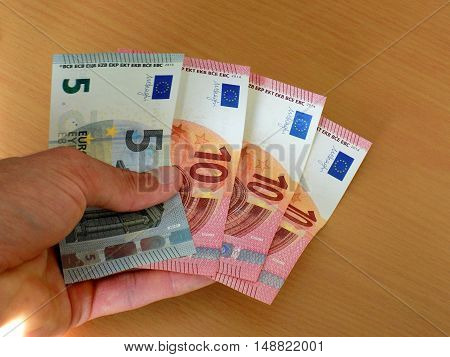 Men holding euro banknotes money on table
