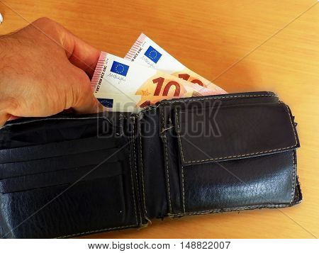 Men pulls out money, euro banknotes of wallet
