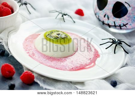 One eye panna cotta with kiwi and raspberry sauce Halloween recipe. Creative idea for kids dessert on holiday party selective focus